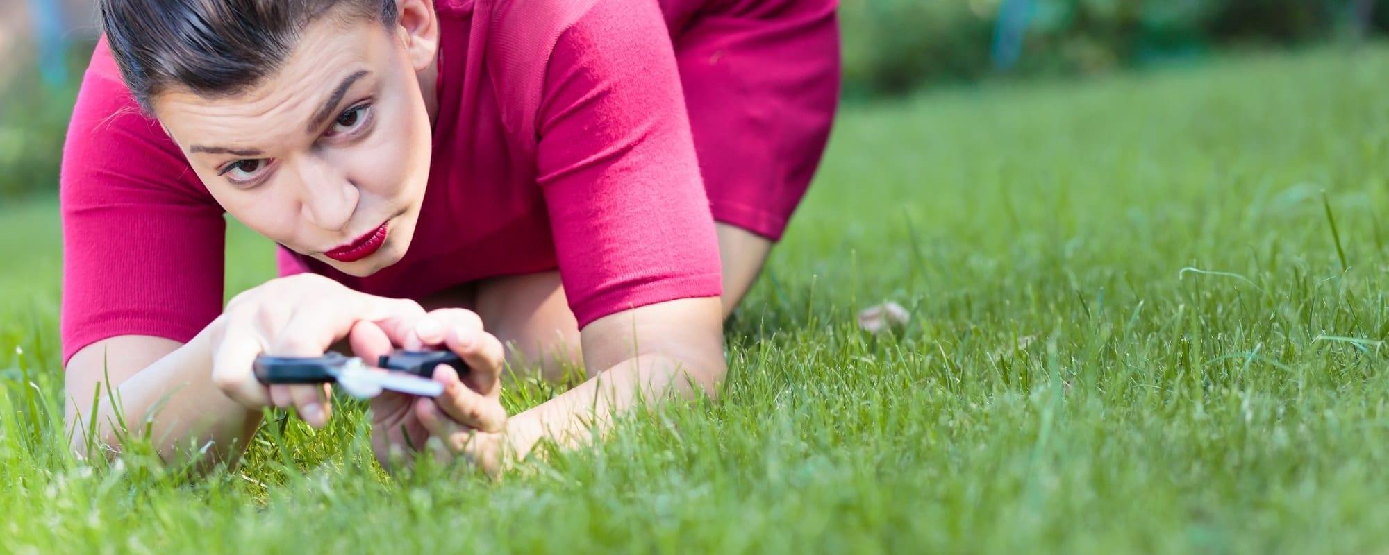 Woman cutting a grass using a scissors